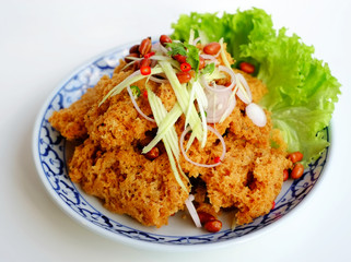 Crispy catfish spicy salad with green mango in blue and white po