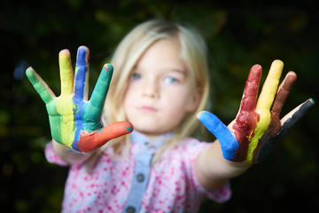cute girl showing her colorful hands. Girl have fun painting her hands outside in the garden.