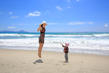 Young pretty woman with little daughter having fun on Sandy Beach