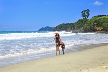 Young pretty woman with her daughter strolling along Sandy Beach