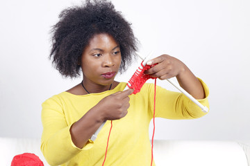 African woman knitting, sitting on a white couch. Knitting something with red colour.