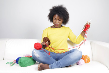 African woman knitting, sitting on a white couch. Surrounded by balls of yarn, she is mixing brown with red colour.