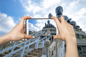 A tourist using smartphone camera taking a photo of Tian Tan Buddha or Big Buddha in Hong Kong