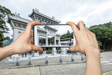 A tourist using smartphone camera taking a photo of the entrance of Tian Tan Buddha in Hong Kong