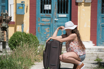Pretty girl with curly hair wear casual clothes, sunglasses and panama hat, waiting with rolling upright suitcase at docks of a traditional train station
