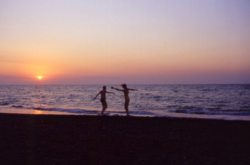ragazzo e ragazza che giocano sulla spiaggia al tramonto