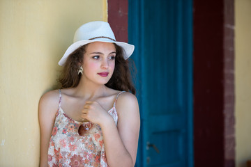 Pretty girl with curly hair wear floral shirt, sunglasses and panama hat, leaning on a yellow wall