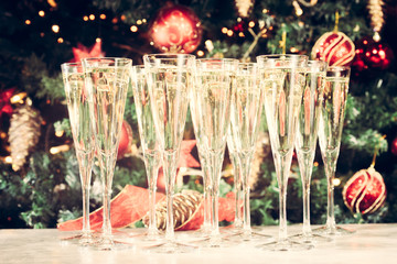 Wall Mural - Glasses of champagne with Christmas tree background. Many glasse