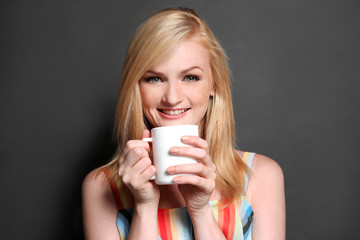 Beautiful girl with cup of coffee on grey background