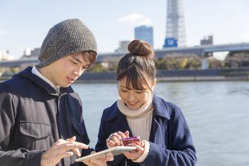 カップル 男女 スマホとタブレット 検索 調べる 外 晴天 隅田川