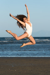 Woman with long curly hair and excellent body wear white monokini, jump high on the air at the beach. Sea and sky as background