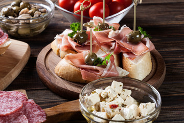 Spanish tapas with slices jamon serrano, salami, olives and chee