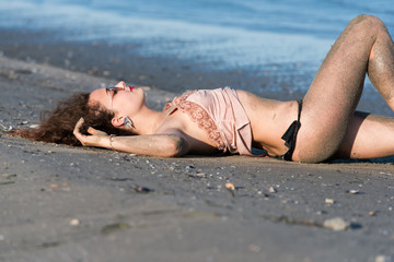 Woman with long curly hair wear bottom bikini, sunglasses and wear spaghetti strap, lying on the beach. Sea as background