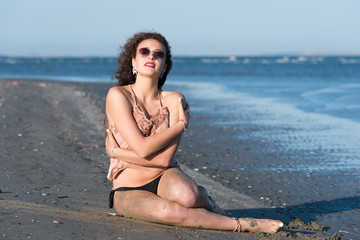 Woman with long curly hair wear bottom bikini, sunglasses and wear spaghetti strap, sitting on the beach. Sea as background