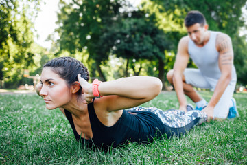Young woman doing exercise with her training partner