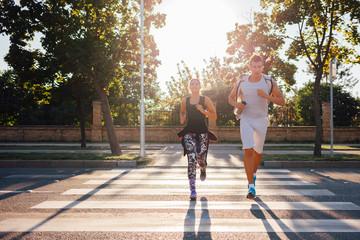 Couple running over a pedestrian crossing
