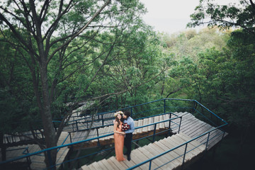 Stylish beautiful happy wedding couple kissing and embracing in Botanical Garden