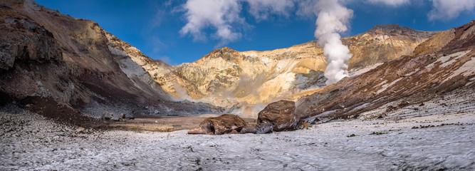Big rocks on the eternal snow inside Mutnovsky volcano crater, Kamchatka, Russia