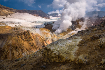 River flowing through the canyon with fumaroles inside Mutnovsky Volcano crater, Kamchatka, Russia