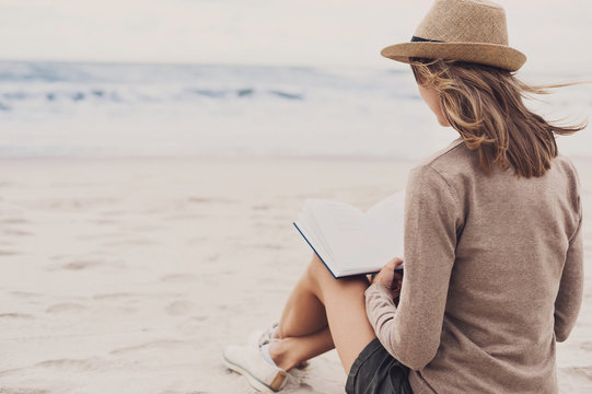 Young woman sitting on the beach and reading a book. Relaxation concept