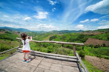 Little girl taking a photograph on viewpoint, Nan Thailand