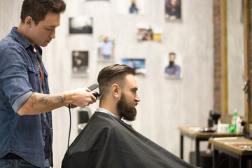 """Side view portrait of handsome young bearded caucasian man getting trendy haircut in modern barbershop. Cool men hair stylist with tattoo """"born barber"""" serving client. Indoors shot"""