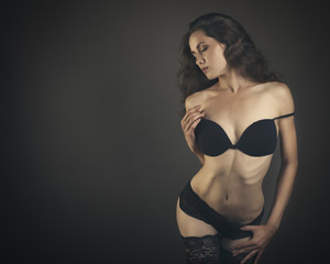Beauty young woman body in black lingerie  on dark background.
