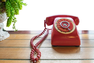 Red telephone vintage old style on wooden table