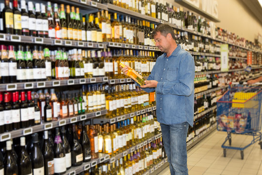 Man looking at bottle of wine in supermarket