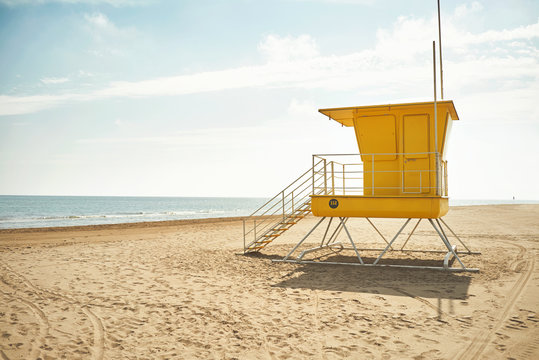 Yellow lifeguard post on an empty sandy beach with the background of blue sky with clouds and the sea