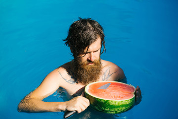 man with watermelon and knife in pool