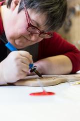 behinderte Frau macht Brandmalerei