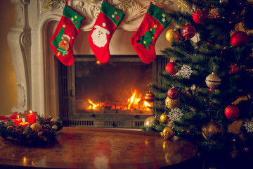 Toned image of wooden table in front of decorated fireplace and