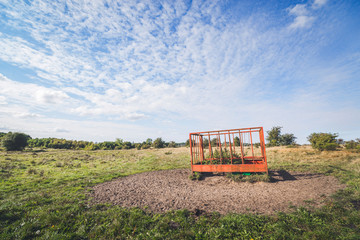 Rural field with a red cage