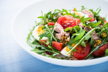 Fresh salad with tuna, tomatoes, eggs, arugula and mustard on blue wooden background close up. Healthy food.