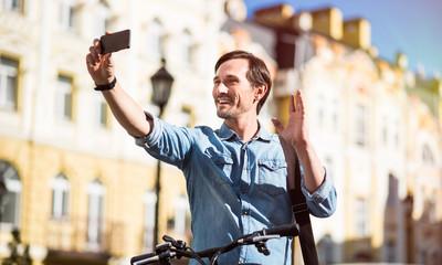 Cheerful man making selfies