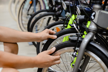 Hand on bicycle tire, sports store background