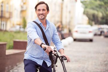 Cheerful man riding a bike