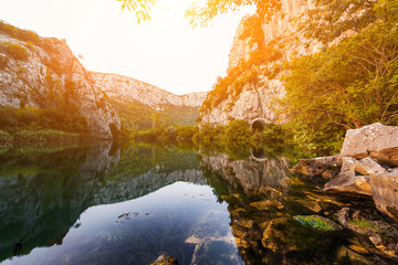 Foto op Aluminium Rivier Gentle sunset light at the canyon of river Cetina, surrounded by rocks and stones, nature landscape with reflection in a water, Omis, Croatia