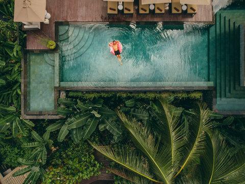 Aerial shot of young man relaxing in resort swimming pool