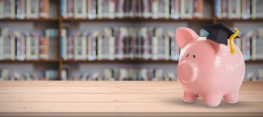 Composite image of piggy bank with graduation hat