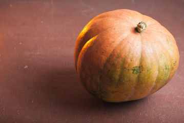 One orange pumpkin on a wooden table