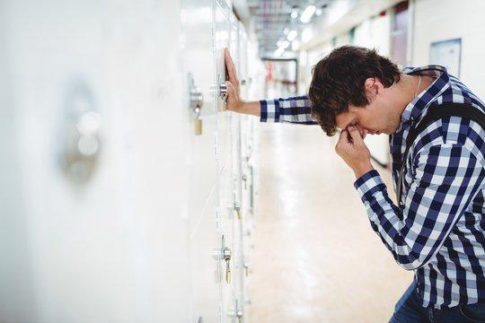 Sad student leaning on locker