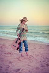 Portrait of a beautiful blond female playing guitar on the beach, sunset sunny blue sky outdoors background