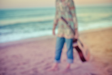 Unfocused photo of elegant woman walking on the beach with guitar, outdoor background
