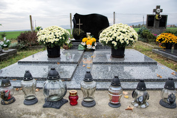 Graves, tombstones and crucifixes on traditional cemetery. Votive candles lantern and flowers on tomb stones in graveyard. All Saints' Day.All Souls' Day. Gravestones in village Tvrdomestice, Slovakia