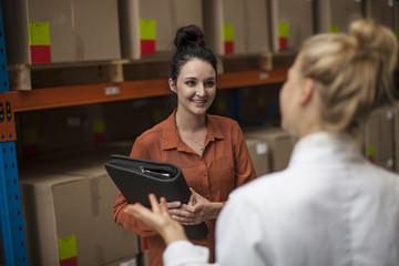 Two women talking in warehouse