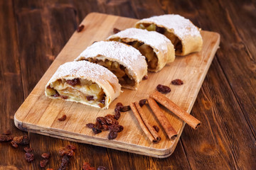 Apple strudel with icing sugar, cinnamon sticks, wooden background