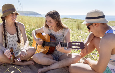Smiling teenage girl playing guitar for her friends on the beach