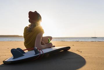 Teenage girl sitting on surfboard, listening music on the beach